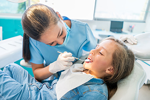 Young girl relaxes comfortably in a dental chair while a dentist inspects her teeth.