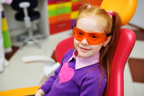 Young red headed girl with pigtails smiling in dental chair